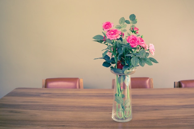 Pink roses in a vase on wooden table