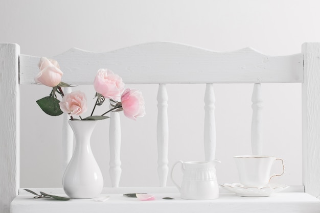 Pink roses on vintage wooden white shelf