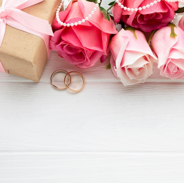 Pink roses and wedding rings with pearls