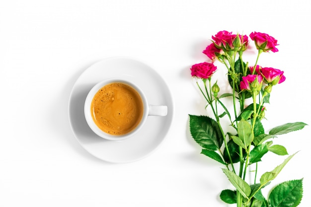Pink roses with a cup of coffee isolated on a white background
