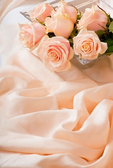 Pink roses with dew drops lies on a delicate silk surface