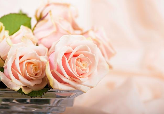 繊細なシルクの表面に露の滴が付いたピンクのバラが横たわっています