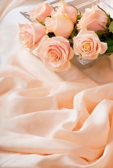 Розовые розы с каплями росы лежат на нежной шелковой поверхности.