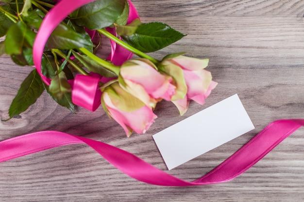木製の背景に空のラベルとピンクのバラ