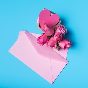 Pink roses with envelope on table