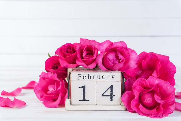 Pink roses with february 14 text on wooden block calendar on wooden background.