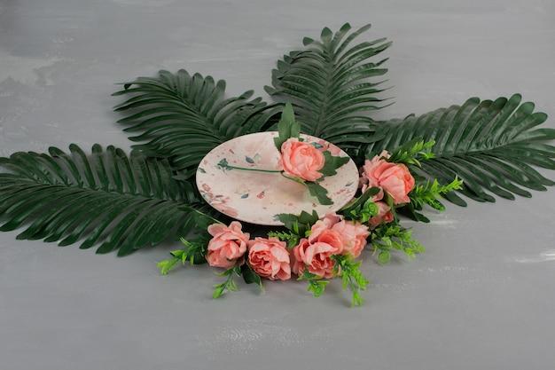 Rose rosa con foglie verdi e piastra su superficie grigia