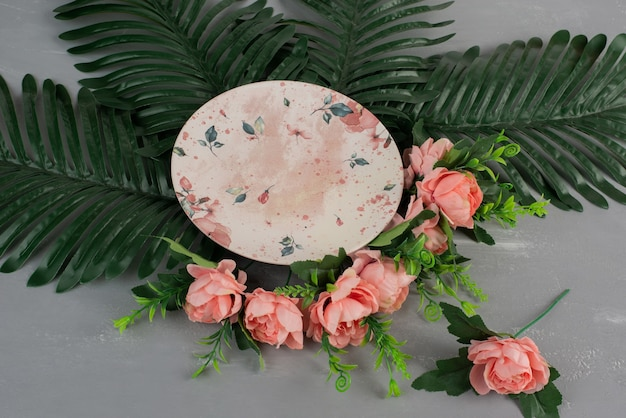 Pink roses with green leaves and plate on grey surface
