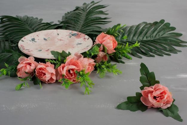 Rose rosa con foglie verdi e piastra su superficie grigia.
