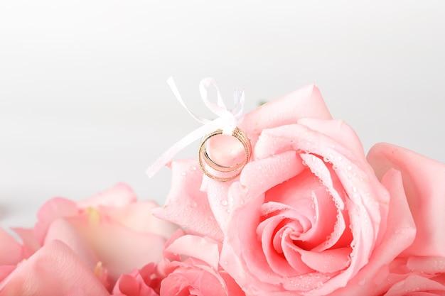 結婚指輪とピンクのバラ。結婚式のロマンチックな背景