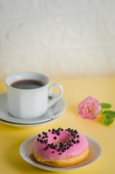 コーヒーガラスと明るい黄色の背景にピンクの丸いドーナツ