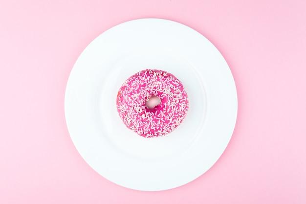 밝은 분홍색 배경에 접시에 핑크 라운드 도넛