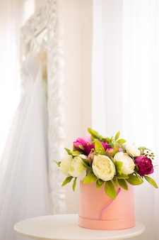 Pink round flower box, inside colorful peonies on the background of a white mirror with a wedding dress
