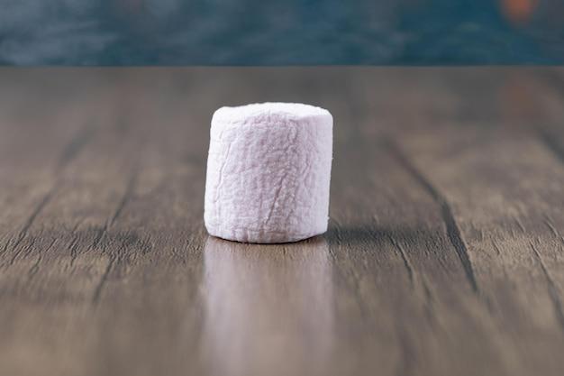 Marshmallow rotondo rosa su fondo di legno.
