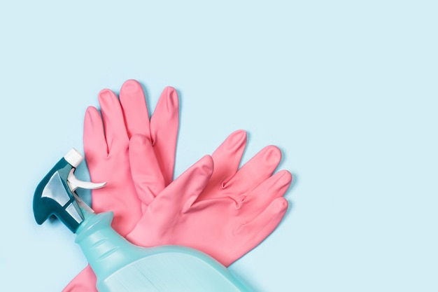 Pink rubber gloves and cleaning product sprayer on a light blue background