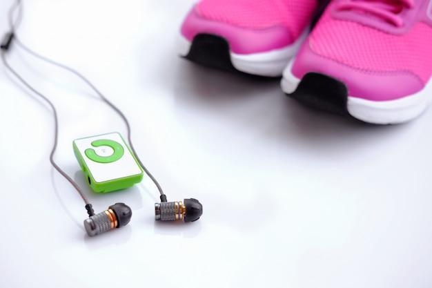 ピンクの女性用ランニングシューズとヘッドフォン付きmp3プレーヤー