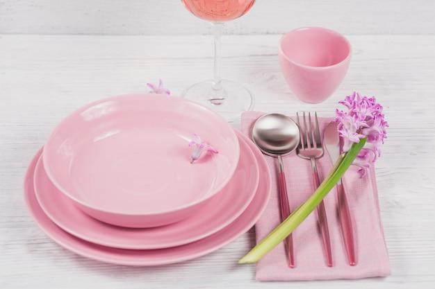 Розовая деревенская обстановка с фиолетовым цветком гиацинта, льняной салфеткой и бокалом розового вина на белой деревянной поверхности