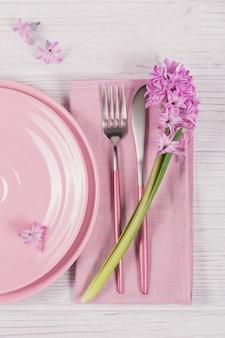 Розовая деревенская сервировка стола с фиолетовым цветком гиацинта и льняной салфеткой на белом деревянном столе