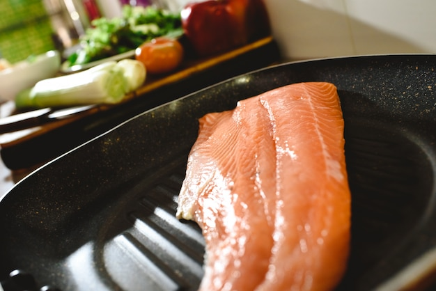 Pink salmon fillet in a frying pan before cooking it.