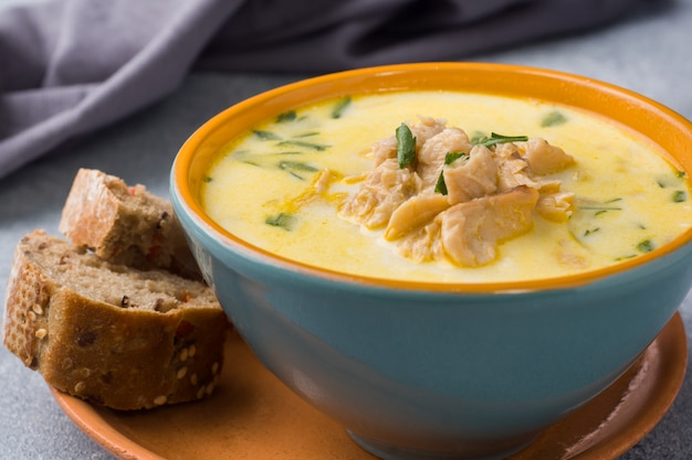 Pink salmon fish soup with cream in a ceramic bowl.