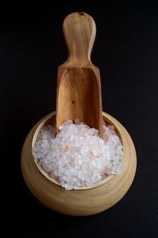 Розовая соль в деревянной миске.
