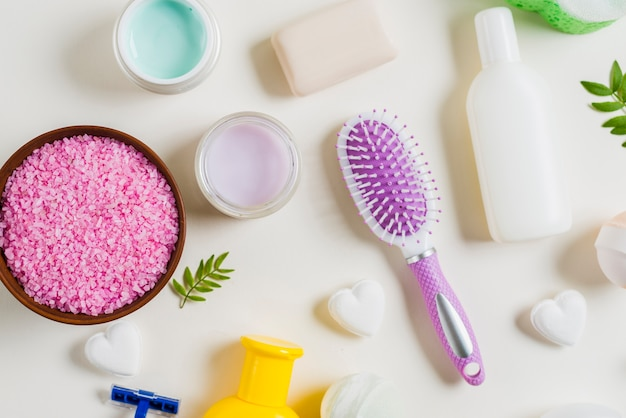 Pink salt; toothbrush and cosmetics products on white backdrop