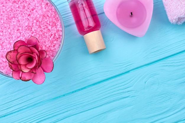 Розовая соль с цветочной бутылкой и свечой на синем дереве. плоский вид сверху.