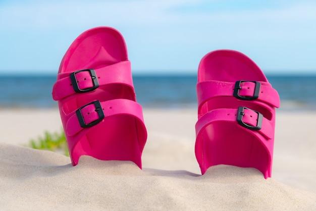 美しい晴れた日のビーチでピンクのサンダル。海沿いの砂の中のスリッパ。