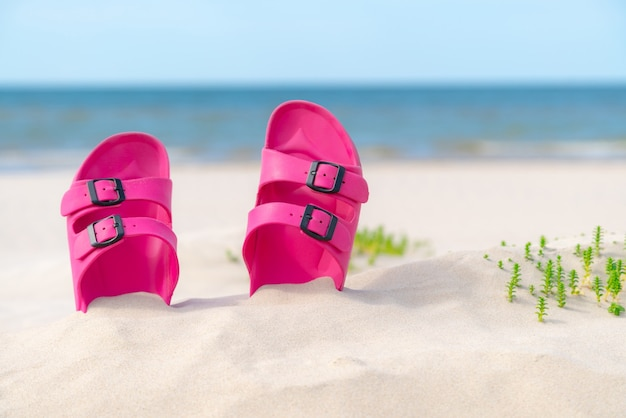 Pink sandals at the beach on a beautiful sunny day