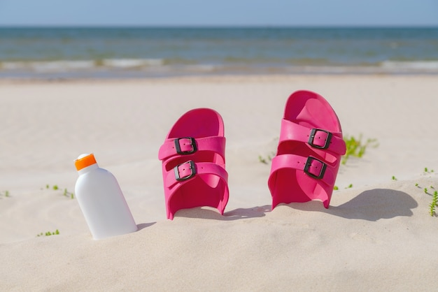Pink sandals, sunglasses and sunscreen at the beach on a beautiful sunny day.