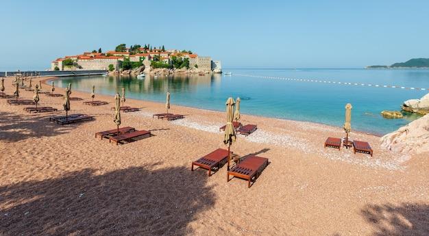 Розовый песчаный пляж милочер и утренний вид на островок святой стефан (черногория, недалеко от будвы). люди до неузнаваемости.