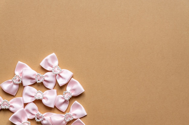 Pink satin bows with pearl hearts pattern on beige background. festive concept for st valentine's day.
