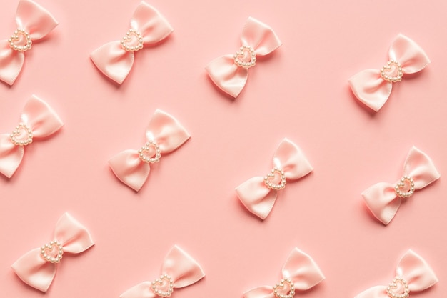 Pink satin bows with pearl hearts pattern on pink background. festive concept for st valentine's day.