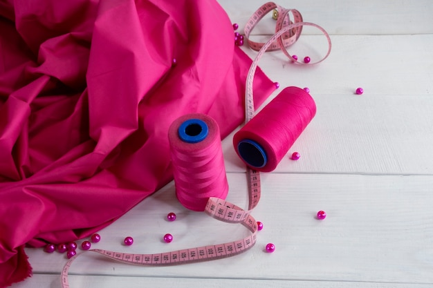 Pink satin fabric with thread and centimeter on wooden background with beads.