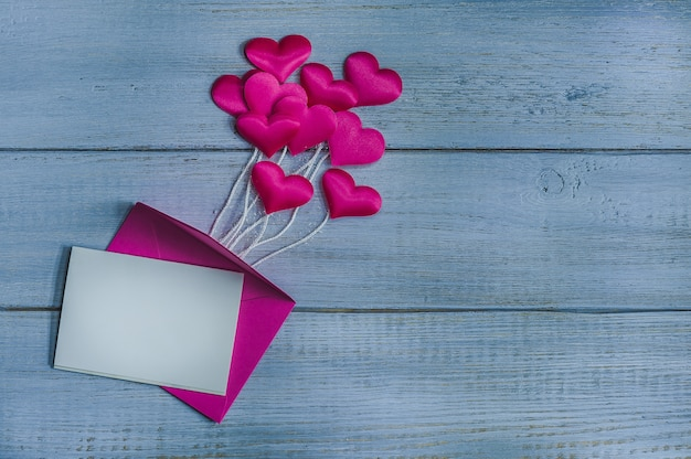 Pink satin hearts above envelope on wooden background