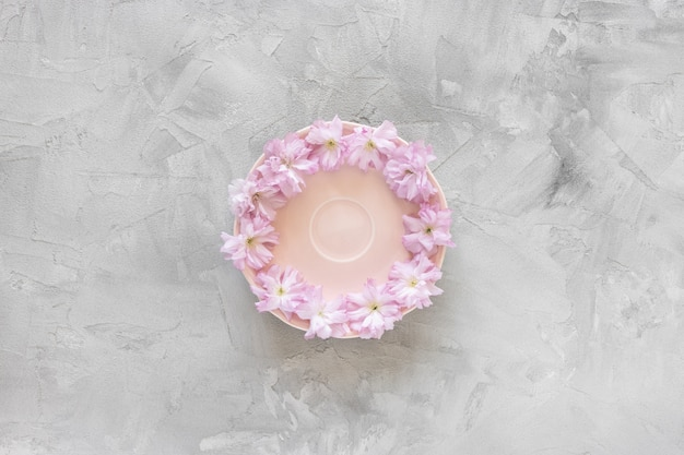 Розовое блюдце и свежие весенние цветы сакуры