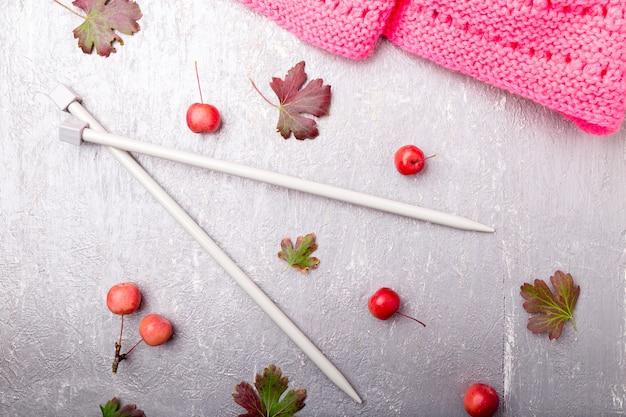 Pink scarf near knitting needles on grey surface,