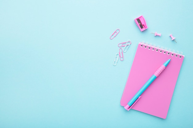 Pink school accessories on blue background