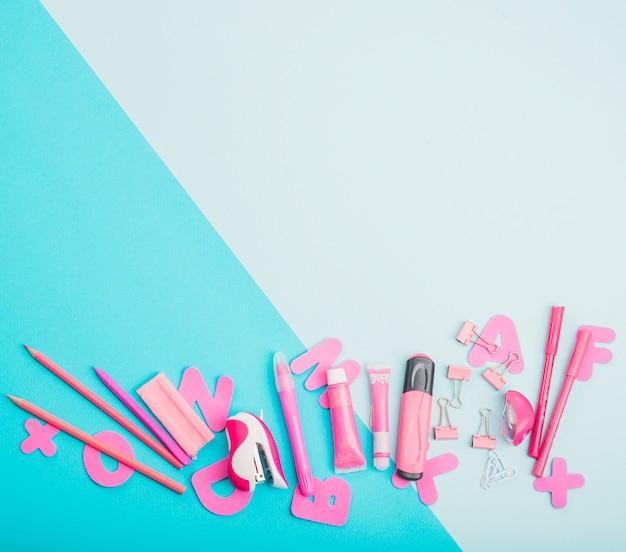 Pink school supplies and alphabets on dual color background