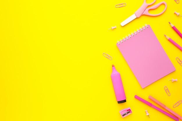 Розовые школьные принадлежности на желтой стене с космосом экземпляра. обратно в школу. квартира лежала.