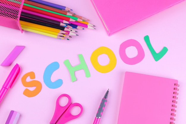Pink school  supplies with an inscription  on a  pink background