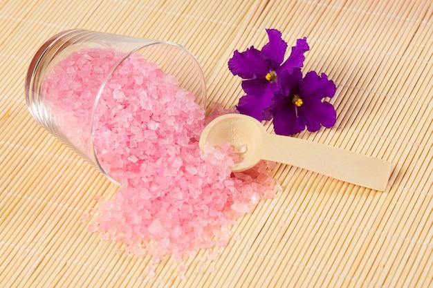 Розовая морская соль для ванны и ложка на бамбуковой циновке
