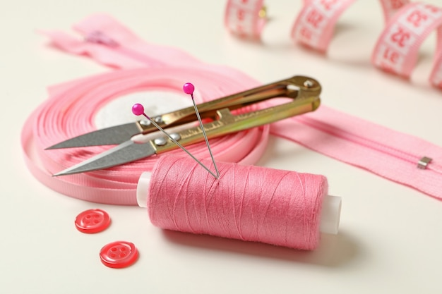 Розовые швейные принадлежности изолированные крупным планом