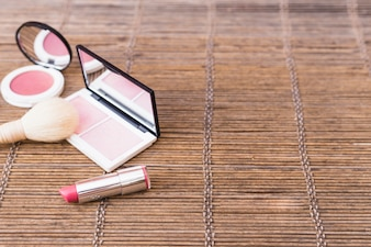 Pink shade blusher palette; makeup brush and lipstick on placemat