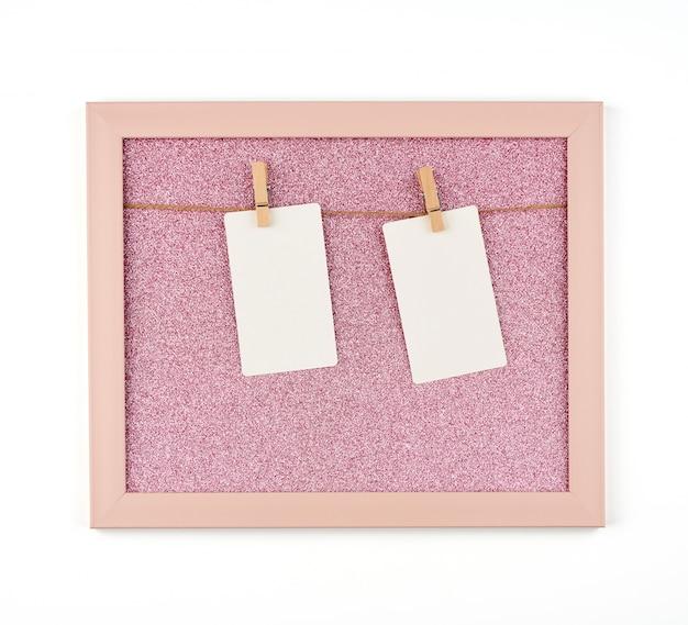 ロープと木製の洗濯はさみに掛かっている空のホワイトペーパーシートとピンクの光沢のあるフレーム