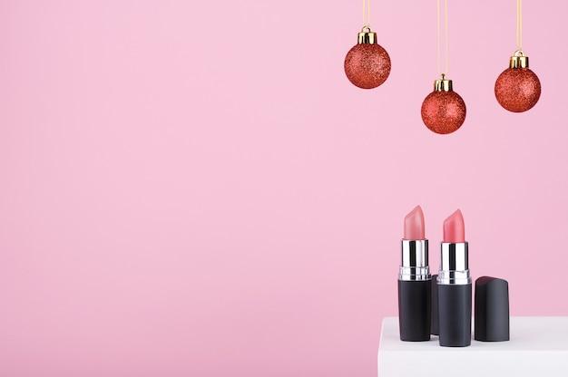 白いスタンドにピンクの光沢のある口紅。女性へのクリスマスプレゼント。美容ツールは、メイクアップアーティストのためのプロのメイクアップのためのアクセサリーです。化粧品のお祝いの装飾。スペースをコピーします。