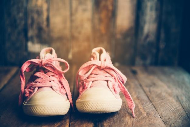 Pink shoes for children on wooden floor