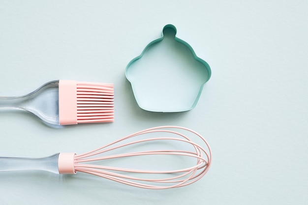 Pink silicone cooking brush, whisk and small metal cookie cutter with pastel color