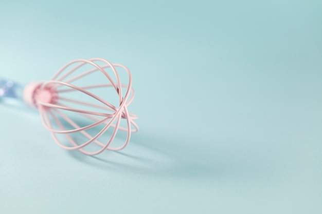 Pink silicone whisk  with clear handle  on blue background, close up