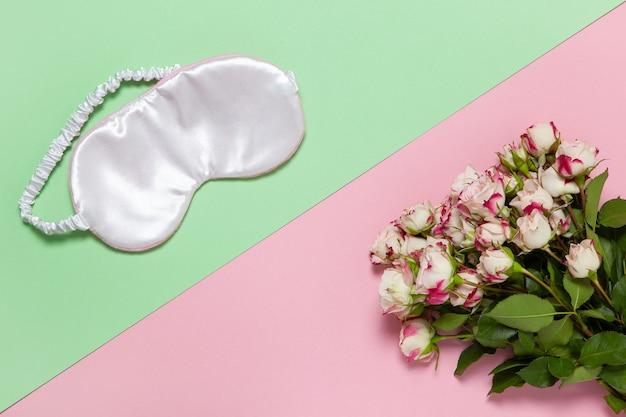 ピンクのシルクスリープマスク、パステルカラーの2色の背景に小さなバラの花束
